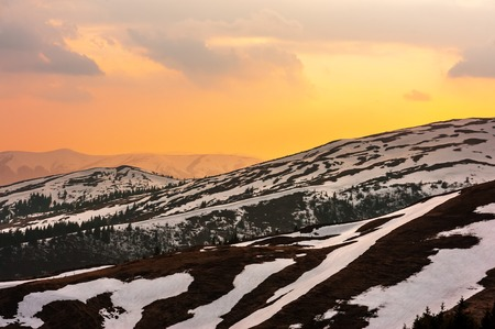 Fantastic spring landscape with snow mountain glowing by evening sunlight. Carpathian mountains. Travel vacations concept Standard-Bild