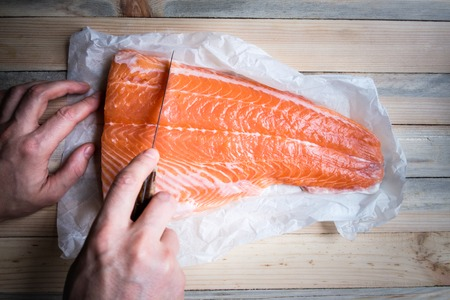 Man cut the fresh fillet of salmon fish on white paper closeup. Food photography
