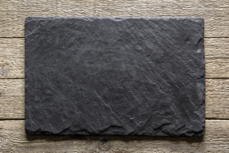 Black slate board on grunge wooden table closeup. Natural texture. Can be used like food background Standard-Bild