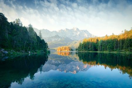 Fantastic sunrise on mountain lake Eibsee, located in the Bavaria, Germany. Dramatic unusual scene. Alps, Europe. Landscape photography