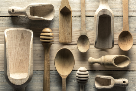 Different wooden utensils on wooden table closeup. Natural food texture background