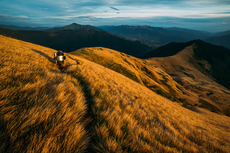 Beautiful Carpathian mountains in autumn time. Alone tourist on grass path. Travel concept background