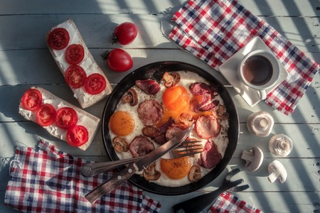 Delicious breakfast with fried eggs, sausage, sandwichs and coffee cup top view. Food photography