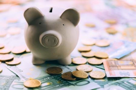 Piggy moneybox with euro cash and coins closeup. Financial concept