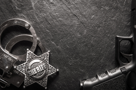 Sheriff star and handcuffs on black slate table closeup. Law concept background Standard-Bild