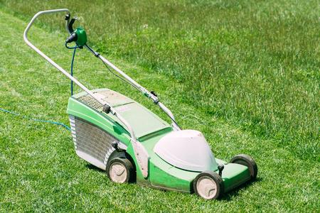 Electric lawn mower on green grass closeup
