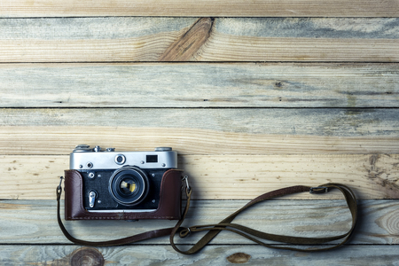 Old vintage film photo camera with brown leather strap on grunge wooden table. Photographe concept background Standard-Bild