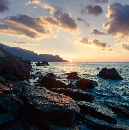 Picturesque seascape on beauty seacost. Rocky beach and waves glowing by sunrice light. Vacations travel concept