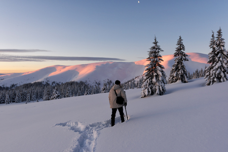 Alone photographer in snowy hills in hight winter mountains in sunrise time. Travel concept. Carpathian mountains. Landscape photography