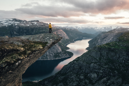Breathtaking view of Trolltunga rock - most spectacular and famous scenic cliff in Norway. Picturesque landscape with sunset sky and clear lake Standard-Bild