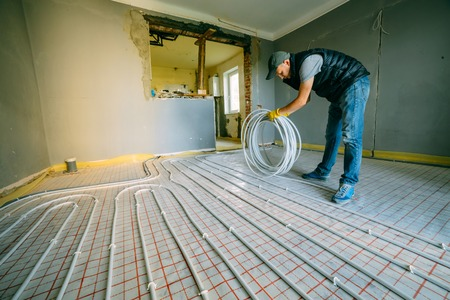 Pipefitter installing system of heating. Repair in the apartment Standard-Bild