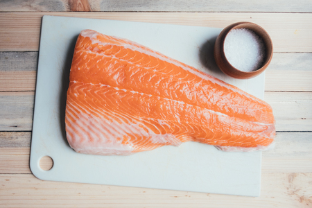 Fresh fillet of salmon fish on white paper closeup. Food photography