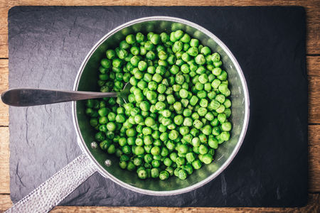 Green peas on silver frying pan on black slate plate. Food photography Standard-Bild