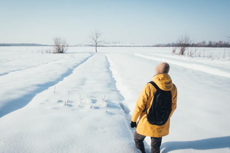 Alone traveler in yellow jacket with black backpack on snowy winter field