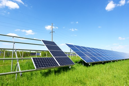 Solar panel installation on blue sky background. Green grass and cloudy sky. Alternative energy concept Stock Photo