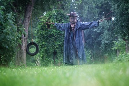 Scary scarecrow in a hat in garden in cloudy weather. Halloween concept
