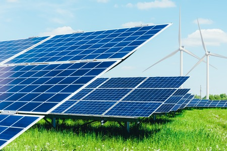 Solarpanel auf blauem Himmelhintergrund. Grünes Gras und bewölkter Himmel. Alternatives Energiekonzept Standard-Bild - 103989890