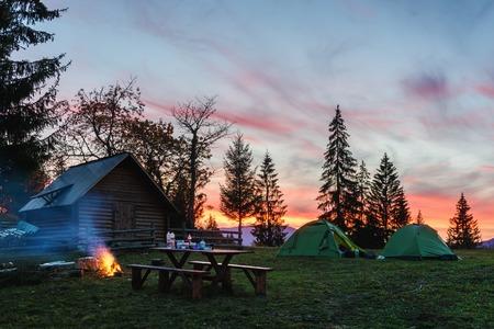 Drei Zelte, die von innen von einer Taschenlampe vor dem Hintergrund eines unglaublichen Sonnenuntergangshimmels beleuchtet wurden. Erstaunliche Abendlandschaft. Tourismuskonzept