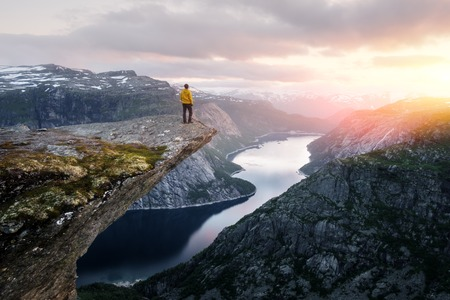 Alone tourist on Trolltunga rock - most spectacular and famous scenic cliff in Norway Reklamní fotografie