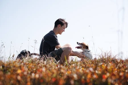Teenager on autumn lawn with small white dog. Friendship and travel concept