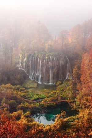 Aerial view on amazing foggy waterfall in Plitvice lakes. Orange autumn forest on background. Plitvice National Park, Croatia. Landscape photography