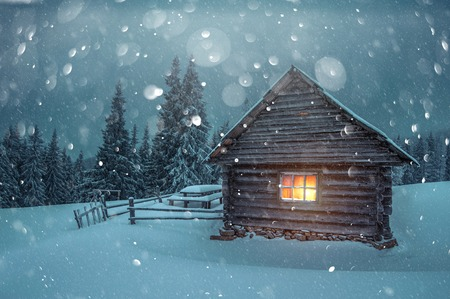 Fantastic winter landscape with wooden house in snowy mountains.
