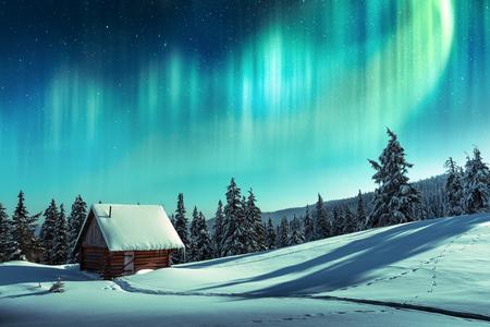 Fantástico paisaje invernal con casa de madera en montañas nevadas y luz del norte en el cielo nocturno Foto de archivo
