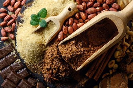 Cocoa powder, chocolate, nuts and spices on a wooden table. Food photography