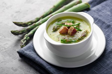Asparagus soup in white bowl closeup. Food photography
