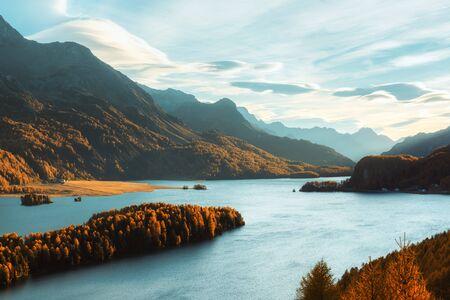 Vista épica sobre el lago de otoño Sils (Silsersee) en los Alpes suizos. Bosque de otoño con alerce amarillo sobre fondo. Fotografía de paisaje Foto de archivo
