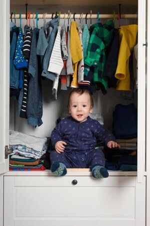 Smiling kid hiden in clothing closet filled with coloured clothes Stockfoto - 130760059