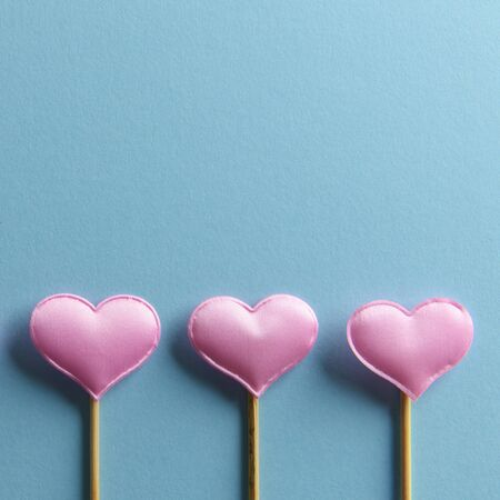 Three pink textile hearts on wooden sticks on blue background. Valentines day background, creative texture and love concept Stock Photo