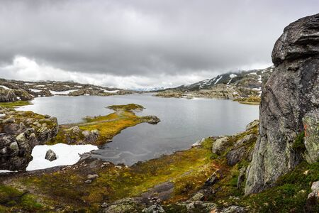 Amazing norwegian landscape with clear lake and snowy mountains Standard-Bild - 130760189