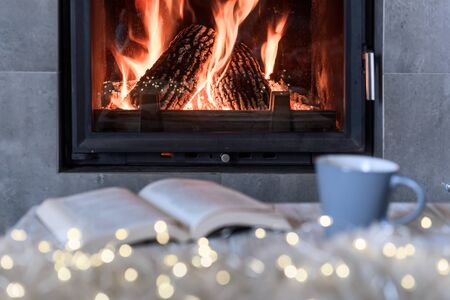 Hygge concept with open book and cup of tea near burning fireplace