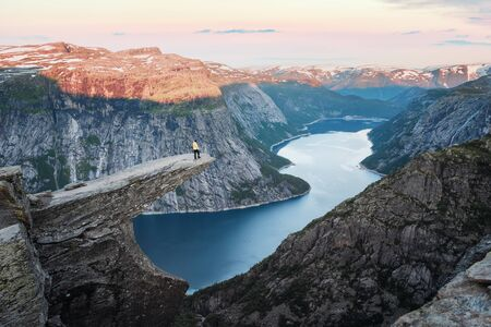 Tourist on Trolltunga rock in Norway mountains. Landscape photography Standard-Bild - 130760214