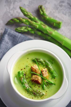 Green asparagus soup in white bowl closeup. Food photography Reklamní fotografie