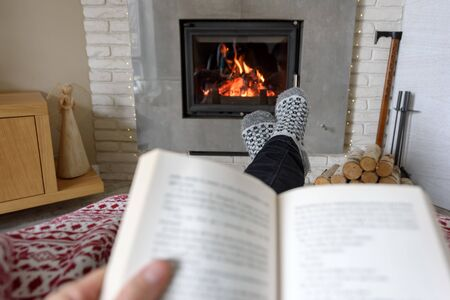 Hygge concept with open book in man hands near burning fireplace