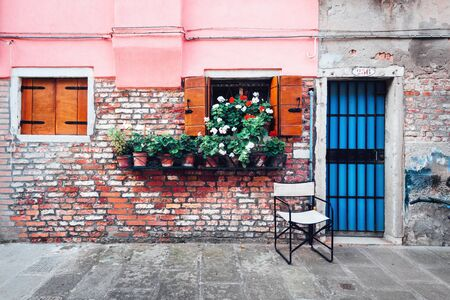 Old italian street with flowers in pots on rustic wall background. Travel background Stok Fotoğraf
