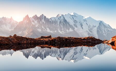 Incredible view of clear water and sky reflection on Chesery lake (Lac De Cheserys) in France Alps.
