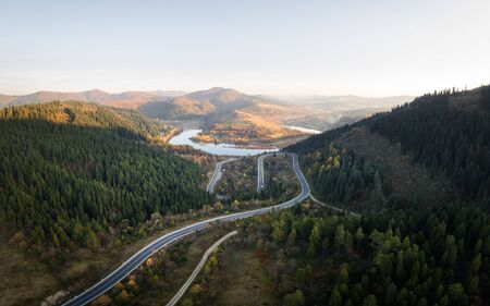 Aerial  view over the autumn mountains with mountain road serpentine, river and forest.