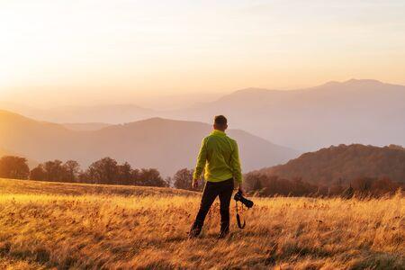Photographer taking photo of autumn landscape with foggy peaks and orange trees