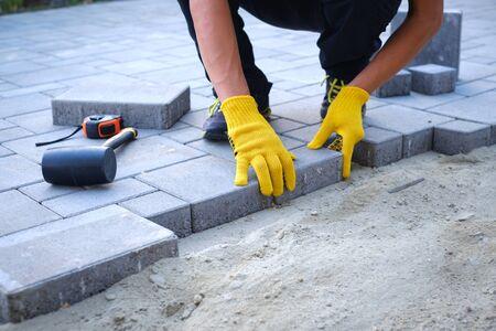 Mistrz w żółtych rękawiczkach układa kostkę brukową warstwami. Kostka ogrodowa z kostki brukowej wykonana przez profesjonalnego brukarza. Układanie szarych betonowych płyt chodnikowych na dziedzińcu domu na podstawie fundamentowej z piasku.