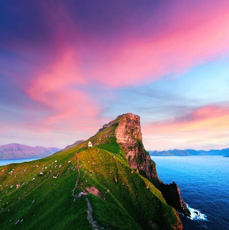 Incredible sunset landscape with Kallur lighthouse on green hills of Kalsoy island, Faroe islands, Denmark
