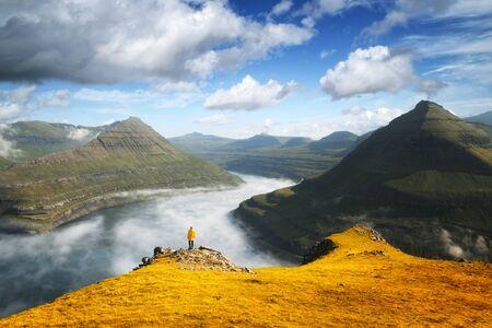 Lonely tourist in yellow jacket looking over majestic foggy fjords of Funningur, Eysturoy island, Faroe Islands. Landscape photography