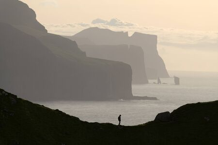 Man silhouette on background of famous Risin og Kellingin rocks and cliffs of Eysturoy and Streymoy Islands seen from Kalsoy Island. Faroe Islands, Denmark. Landscape photography 版權商用圖片
