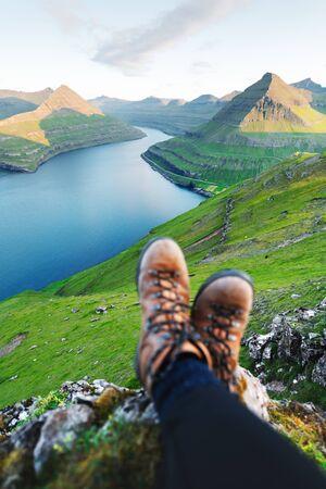 Boots of lonely tourist over majestic fjords of Funningur, Eysturoy island, Faroe Islands. Landscape photography