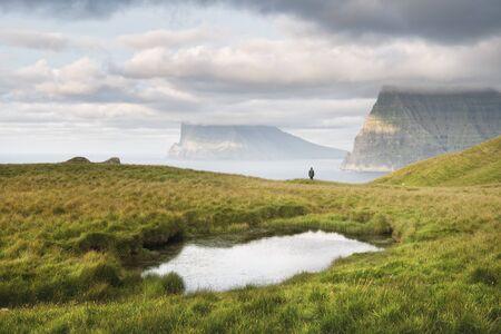 Lonely tourist near small lake looks at foggy islands in Atlantic ocean from Kalsoy island, Faroe Islands, Denmark. Landscape photography Фото со стока