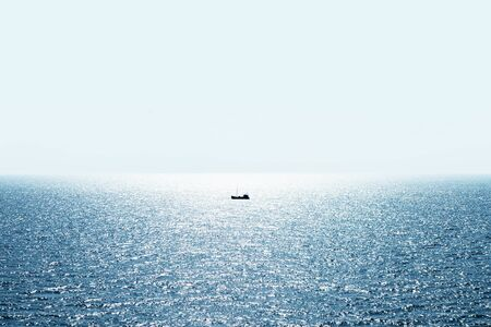 Lonely fishing ship trawler boat on ocean water. Calm clear sea sunny weather. Beautiful horizon of seascape