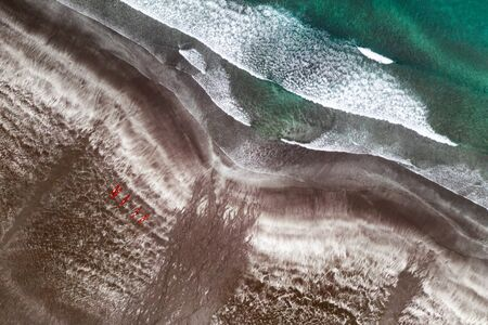 Aerial view of black sand beach and ocean waves. Red kayaks ready for swimming