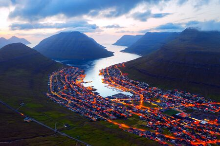 Fantastic aerial evening cityscape of Klaksvik town with glowing streets and fjord, Bordoy island, Faroe islands, Denmark. Landscape photography